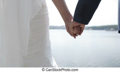 bride and groom hold hands on a blue lake background.