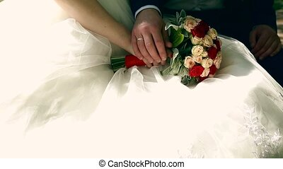 Bride and groom holding bridal bouquet close up