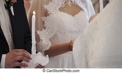 Bride and groom holding candles in church at ceremony -...