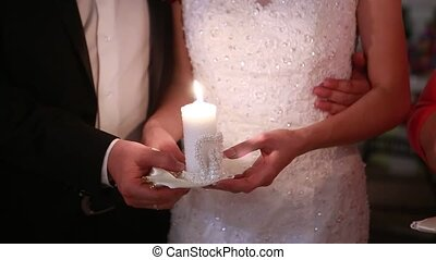 bride and groom holding candles in their hands