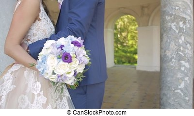 Bride and groom holding colourful wedding bouquet. Marriage...