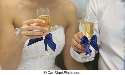Bride and groom holding glasses of wine. Close-up