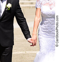 Bride and groom holding hands an walking in new life