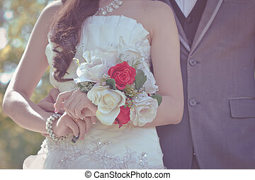 Bride and groom holding hands and a bouquet of beautiful flowers