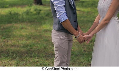 Bride and groom holding hands. at a photo shoot on the wedding day