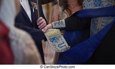 Bride and groom holding hands in church at ceremony - Bride...