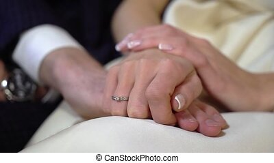 Bride and groom holding hands indoors