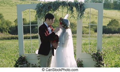 Bride And Groom Holding Hands Near Wedding Arch