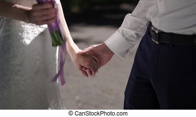 Bride and groom holding hands slow motion