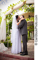 Bride and groom hugging and kissing under wedding arch