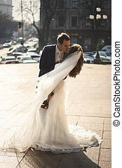 bride and groom hugging at windy day on city street