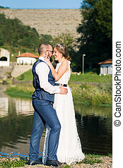 Bride and groom hugging in front of a lake