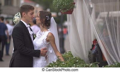 Bride and groom hugging on the street, the bride holding a bouquet