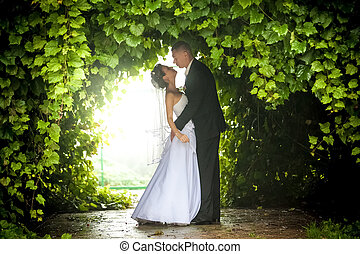 Bride and groom hugging under trees