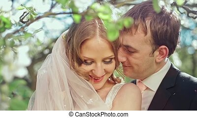Bride and Groom in a Blooming Apple Garden