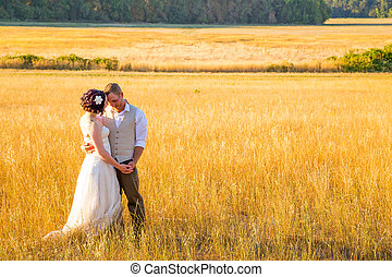 Bride and Groom in a Field at Sunset