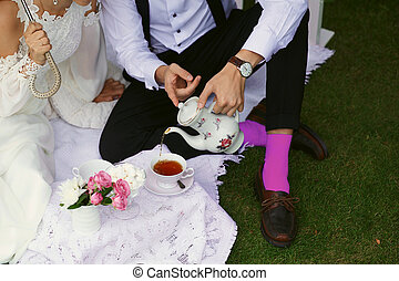 Bride and groom in bright clothes on the green grass