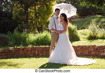 Bride and groom in garden wedding with parasol