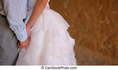 bride and groom in gentle embrace on background of old castle