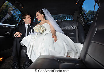 Bride and Groom in Limo - Newlywed bride and bridegroom in...