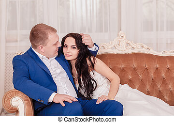 Bride and groom in luxury hotel, kissing on a sofa
