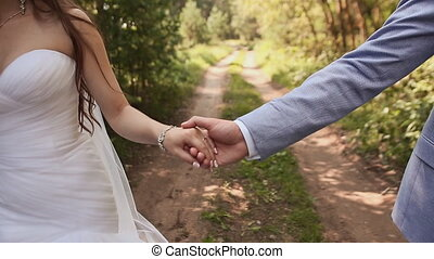 Bride and groom in the forest. They walk together, holding hands. Hands close-up. Happy together. Wedding day.