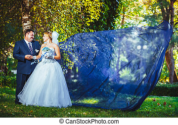 Bride and groom in the park with flying fabric.