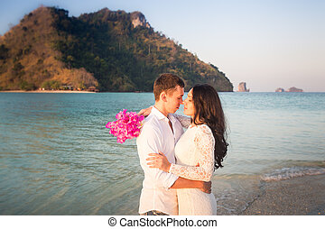 bride and groom kiss against rocky island