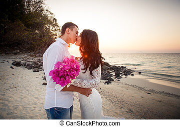 bride and groom kiss at  beach at dawn