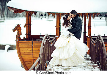 Bride and groom kiss in the front of a wooden boat covered with snow