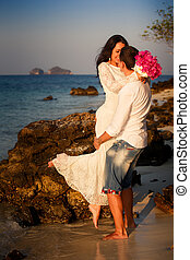 bride and groom kiss on rock at beach