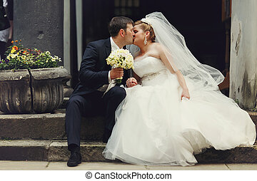 Bride and groom kiss on the old stone stairs