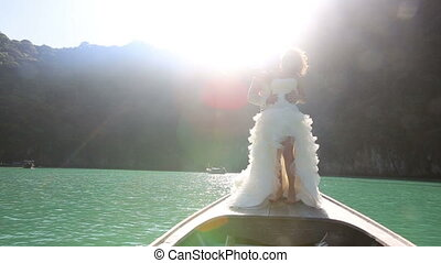 bride and groom kiss standing on longtail boat at backlight