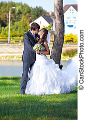 Bride and groom kissing at park against river