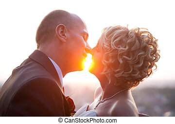 Bride and groom kissing at sunset