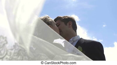 Bride and groom kissing each other outside on a sunny day on...
