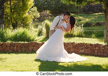 Bride and groom kissing in garden wedding - Bride and groom...