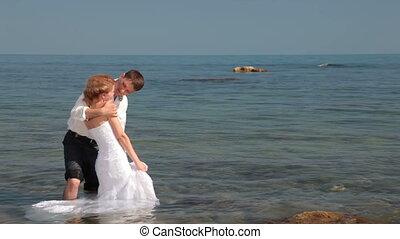 bride and groom kissing near  sea