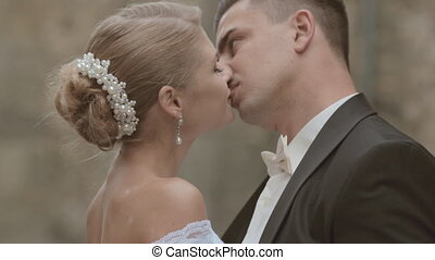 Bride and groom kissing near the walls of a castle