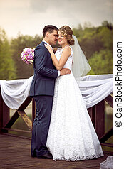 bride and groom kissing on river pier at sunny day