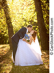 bride and groom kissing passionately at autumn park