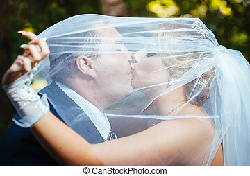 Bride And Groom Kissing Under Veil Holding Flower Bouquet In Hand.