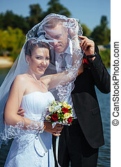 Bride And Groom Kissing Under Veil Holding Flower Bouquet In Hand