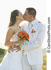 bride and groom kissing with isolat