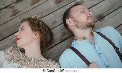 Bride and groom lay on the wooden pier