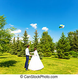 bride and groom look balloon in blue sky