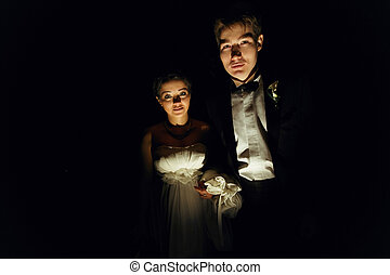 Bride and groom look mysterious standing in the dark room