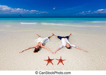 Bride and Groom lying on beach shore with two starfish -...
