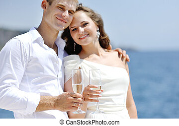 bride and groom making a toast by the sea in wedding day