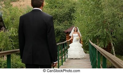 Bride And Groom On A Bridge - Bride and groom embracing and...